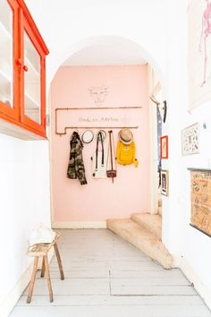 Pink walls in the hallway / entrance of a quirky Dutch home with fab colours (and lots of art).