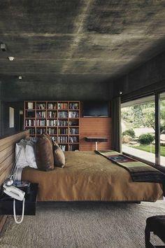 O quarto de casal vem com materiais como o concreto e a madeira.