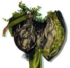 This striking wide-brimmed bonnet (c.1828-32) is made with a wire form covered with silk and lined in linen. Four-inch-wide green silk ribbon borders the brim, decorates the crown and fashions long ties on each side. A black netting ruffle forms a skirt at the back neck.