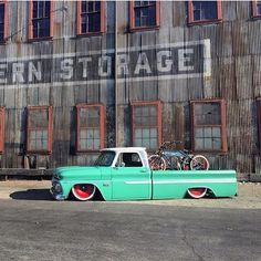 1964 1965 1966 C10 Chevrolet long bed teal pickup on red solid wheels and loaded up with custom bicycle in the bed.