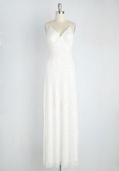 Raising your flute of champagne high, you make a toast to this ravishing white dress! From the sultry V-neckline and padded bust to the crisscrossing back and decoratively detailed sequins, this gorgeous gown is an ensemble that you will happily celebrate for years to come.