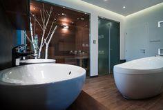 A kép tökéletesen ábrázolja, hogy a természetes és a modern elemek egyvelege miként kristályosodik ki egy páratlan fürdőszobában. Itt a reggeli készülődés felfrissítő motivációt ad a napra és az esti rutin pedig egyenesen egy wellness élménnyé válik. 🛁 Az egyedi, épített cédrus szauna pedig már csak hab a tortán, melyben az SLV Brick és Spot lámpák ideális fényvilágot teremtenek. 💡 Keltsd életre Te is a fürdőszobád a minőségi lámpáink és fürdőszobai kiegészítőink segítségével! ✅ Nautilus, Bathtub, Bathroom, Standing Bath, Washroom, Bathtubs, Bath Tube, Full Bath, Bath