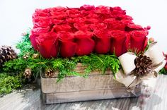 Romantic Pine Crate  Roses are without a doubt the flower of romance. This beautiful arrangement embodies the best colors of all, passion and the holiday season. Thirty-six lush red roses sit upright, with vibrant Christmas greens that sit beneath. A pinecone and gold bow tie everything together.
