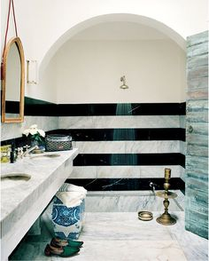 I'm a fan of arches and well-defined spaces.  The lack of a shower curtain makes this shower feel open and luxurious.  (Moroccan Home of Bruno Frisoni and Hervé Van der Straeten, Vogue)