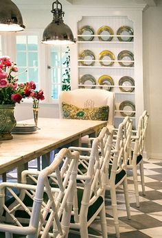 CLASSIC DINNING ROOM, BLACK/WHITE FLOOR,NICE FRETWORK CHAIRS,MIXED WITH UPHOLSTERED CHAIRS LOVELY LARGE TABLE..NICE BUILT IN FOR DINNERWARE NICE NATURAL LIGHT.. VINTAGE LIGHT FIXTURES .AND ALWAYS LOVE THE FLORALS!!! ..