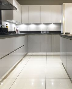 Grey gloss kitchen with white cupboards above and black worktop and mirrored plinth