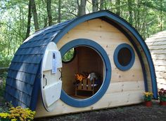 Hobbit Hole Playhouse with round front door and windows, all natural wood construction, blue trim