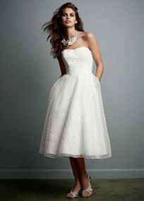 Elegant but distinctive, this short a-line gown is ideal wedding dress for the bride who revels in her fashionable individuality.  Dotted organza tea length gown is ideal for any wedding event and is also a terrific choice for a reception dress.  Gown has a natural waist which can be played up with a sash.  No Train. Sizes 0-14.  Ivory available online and in limited stores.