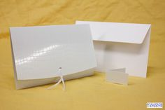 Partecipazione con copertina in cartoncino lavorato di colore bianco lucido.  A rifinire la copertina un nastro di colore bianco.  All'interno un intercalare in cartoncino perlato con decori in argento a caldo.  Completa di invito realizzato su cartoncino perlato con decori in argento a caldo.  Formato 17 x 11,5 cm.  ARTICOLO MADE IN ITALY