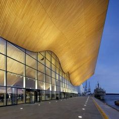 Undulating oak walls burst through the glazed facade of this concert hall
