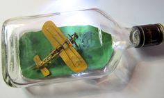 Vad gör man med en platt tom 37 cl 'pocketflaska'. Man fyller den med ett flygplan. Här Louis Bleriots flygplan som var den första som flög över engelska kanalen den 25 juli 1909. Lite knepigt flaskjobb med tanke på det begränsade 'svängrummet' i flaskan. Det blev relativt hyfsat....