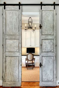 Traditional Home Office with Built-in bookshelf, Barn door, Hanging rustic door, Chandelier, Hardwood floors, Crown molding