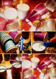 CORDÃO DE LUZINHAS  Material • um cordão de luzinhas • alguns copinhos (podem ser grandes ou pequenos, aqui estamos fazendo com um de 70ml) • estilete  Faça um pequeno corte, de no máximo 1cm, no fundo de cada copo. Encaixe uma luzinha em cada corte. Não precisa ter copos em todas as lâmpadas. Voilá!