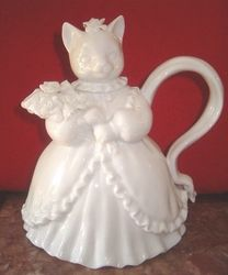 Your guests will be delighted when you serve their tea from our elegant porcelain Miss Kitty Teapot. Dressed in a full gown with ribbons, bows, and hand made roses, she holds 24 ounces and stands 7 1/2