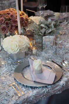 This roses-galore setting features three-dimensional silver floral linens, a rose wrapped in rhinestones, and silver and mirrored vessels.  <i>(Photo: Colin Miller)</i>