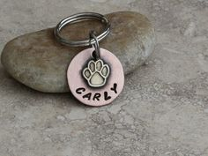 "Tiny paw name tag to be used as a kitten tag, cat tag, dog tag, puppy ID, key chain etc. This tiny 3/4"" copper and brass tag can be used for a tag for that small kitten, a dog tag for the toy breed Chihuahua, a personalized purse charm, backpack zipper pull, Gym or Golf bag ID, or a number of other things. We can stamp a name along the bottom and a phone number on the back. Materials/Measurements 18G Pure Copper .75"" disc Brass paw charm Stainless steel split rings Please know that these..."