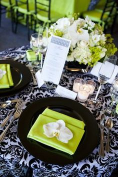 Black & White damask tablecloths, with black chargers and green napkins. This could easily be brightened with mixing in the orange & fushia! Cool for elegant outdoor.