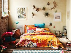 The perfect bedroom. Bright boho bedspread, mounted antler collection, exposed brick, timber floorboards... Bliss.