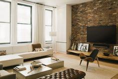 Idea soggiorno moderno industriale. Materiali naturali, colori della terra, grandi finestre e mattoni a vista