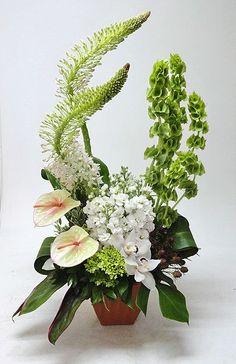 Avante Gardens Florist    Sympathy arrangement featuring eremurus, bells of Ireland, anthurium, hydrangea, cymbidium orchids and stock