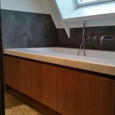 Eiken kasten onder het bad geven behalve bergruimte ook veel warmte aan deze badkamer te Bornerbroek.