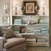 Ideas for accessorizing bookcases-an easy way to change the look of a room and enhance its visual impact. Soft hues of blue, white and beige set the stage for a master bathroom furnished with a comfy lounge chair and a beautifully accessorized bookcase.