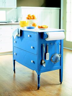 Make a kitchen island out of a dresser by adding casters, a few hooks, a durable top, and a paper towel holder.