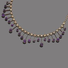 An amethyst and seed pearl necklace, circa 1900 Set to the front with a row of seed-pearls, supporting an undulating fringe of circular mixed-cut amethysts on knife-wire connectors, length 43.5cm.
