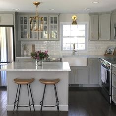 Gray kitchen features gray shaker cabinets adorned with brass pulls by Lewis Dolan paired with honed carrera marble…