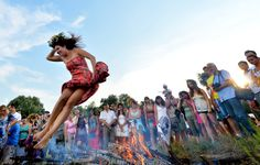 A girl jumps over a campfire while celebrating Ivan Kupala Night, a traditional Slavic holiday not far from Kiev on July 6, 2013. During the...