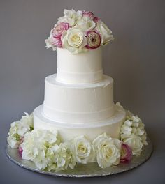 Decorating a wedding cake with fresh flowers.