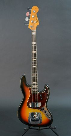 1966 Fender Jazz Bass, VG+, Sunburst, all orig., no issues, double cut solid body, 2 pu,s., oval paddle tuners, rwd neck w/ block inlays, tortious guard, both chrome covers, body shows slight wear ...