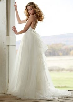 This dress has been popping up all over Pinterest, and with good reason. The open back and low-set bow, the doubled thin straps, and billowy organza and tulle layered skirt — all make for a perfectly gorgeous summer wedding dress. …
