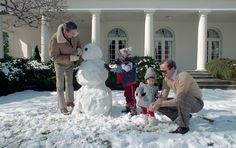 Ronald Reagan making snowman with his son and grandkids outside the White House.