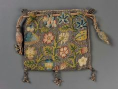 Drawstring bag late 16th early 17th century. England. 12x13 cm. linen plain weave embroidered with silk and silver metallic threads. Braded silk and metallic cords and tassels.