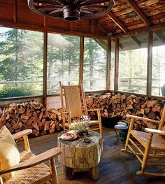 """Firewood is stacked in the screen porch of Deer Cabin, which serves as an """"on-site pied-à-terre"""" while the couple's main house on the property is being built."""