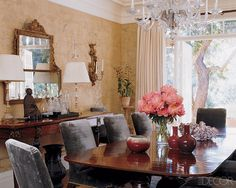 The dining room features Tyler chairs from the Jasper collection by Michael S. Smith, a Regency mahogany table, a George II gilt-wood overmantel mirror, and custom-made De Gournay  wallpaper.