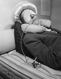 Circa 1950. Garry Moore uses a special device for smoking to prevent the burning of his bedclothes should he fall asleep with a lit cigarette. Photograph by Bettmann/Corbis.