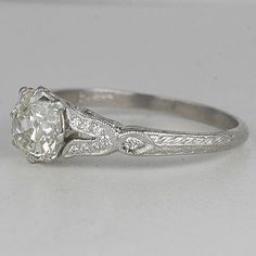 Center antique cushion cut diamond weighs 1.57 carats,I color and SI1 clarity. This vintage diamond is set low in a platinum ring with an edwardian inspired crown basket cradled by diamond studded tulip-shaped V sides. The ring addditional has an elegant detailed design. This ring is an exact replica of an original art deco antique engagement ring.