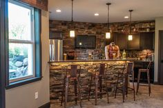 The Stone Accent Adds A Rustic Feel To The Basement Bar In This New Home.