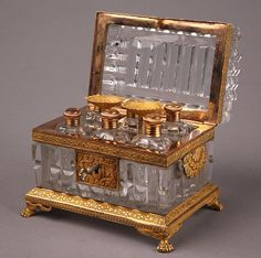 A Charles X crystal and giltbronze mount casket with six perfume bottles. Very finely chiseled and decorated with flowers and resting on four lions paws. Very good condition. Charles X Period, Circa: 1820.