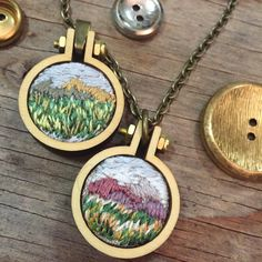 Sarah Buckley, aka IttyBittyBunnies, encapsulates beautiful natural landscapes into miniature embroidered pendants. Working in hoops that fit onto the tips of her fingers, she stitches mountains, cacti, and forests with impressive detail. The finished pieces are then attached to an antique bronze chain and worn as a one-of-a-kind necklace. Embroidering at such a small scale allows Buckley capture the essence of a setting. Instead of showcasing every rock, leaf, or blade of grass, she…