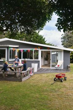 Laid-back Waikanae bach - NZ House & Garden. Rear deck and kitchen servery window.