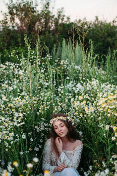 Stock photo of Front view portrait of attractive young woman with long hair wearing camomile wreath and daydreaming in the field of wild flowers by lileinaya