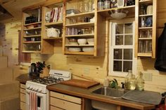 Nice Tiny house kitchen with full stove and OVEN - yes. They later put red cabinet fronts on to match those around the frig. Erin and Dondi's tiny house.