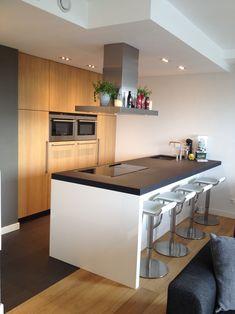 Design keuken. Kookeiland hooglans wit met zwart gebrand composiet blad. Kastenwand eiken geolied