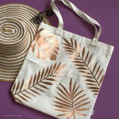 DIY Tropical Tote Bag Because we can't always spend our time in the sand we designed this DIY tropical tote bag so we could take an island breeze with us wherever we go. The post DIY Tropical Tote Bag appeared first on Bag Diy. Diy Tote Bag, Diy Bags, Reusable Tote Bags, Crafts To Make And Sell, Sell Diy, Fabric Bags, Fabric Handbags, Cotton Bag, Fabric Painting