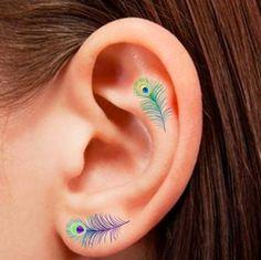 Unas sutiles plumas de pavo real llenas de colores. | 19 Tatuajes lindísimos que se verán perfectos en tus orejas