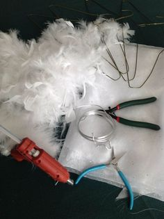 Gather materials like wire coat hangers, heavy gauge wire, pliers, nippers, shiny or glittery fabric, feathers and lots and lots of hot melt glue.