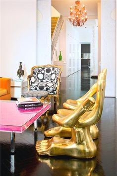 Eclectic living room #design with #lucite coffee table, #gold hand #chair, and ebonized wood #floors